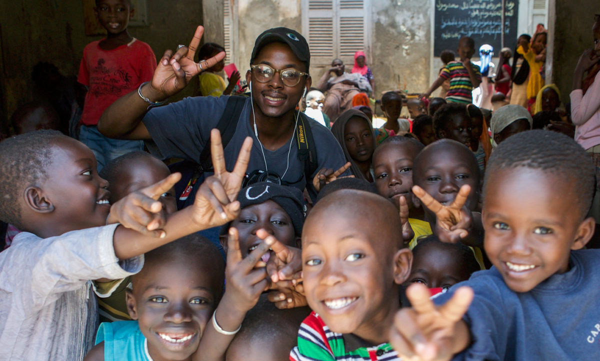 A man and a group of children making the peace signs.