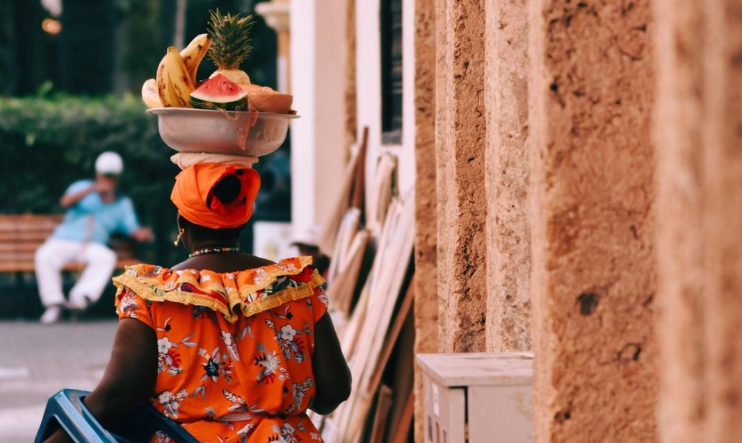Woman carrying a bowl of fruit on her head