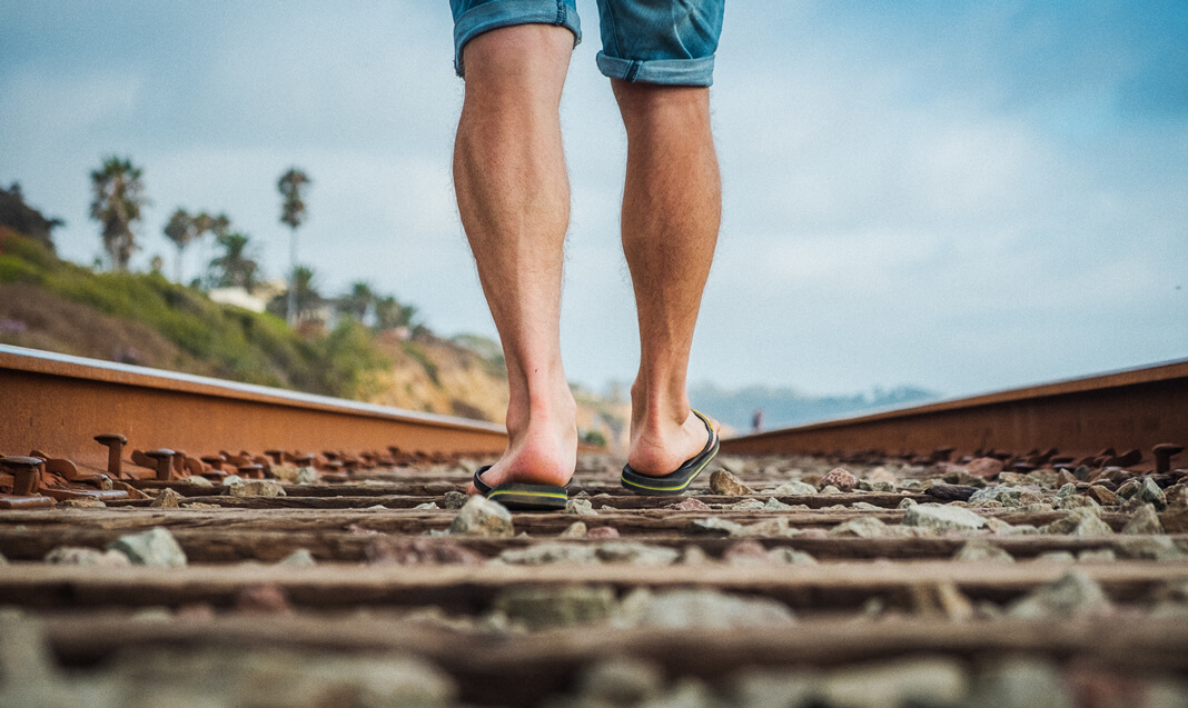 The bottom of someone's legs are seen walking down a railroad track.