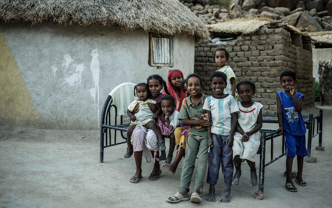 Kids and a woman sit on a bed frame outside a hut
