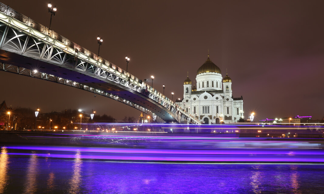 Water shines purple underneath a bridge and building