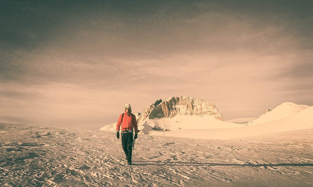 A man walks through the snow with a small peak behind him