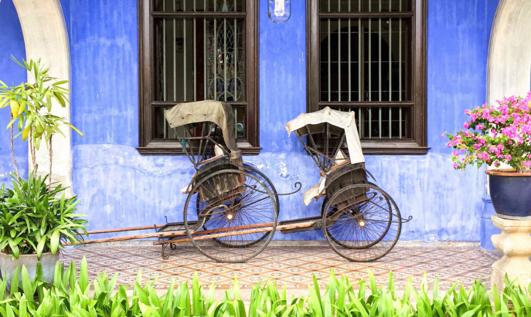 Tuk-tuks in front of a blue wall in Georgetown. Photo by Nazirul Hakim.