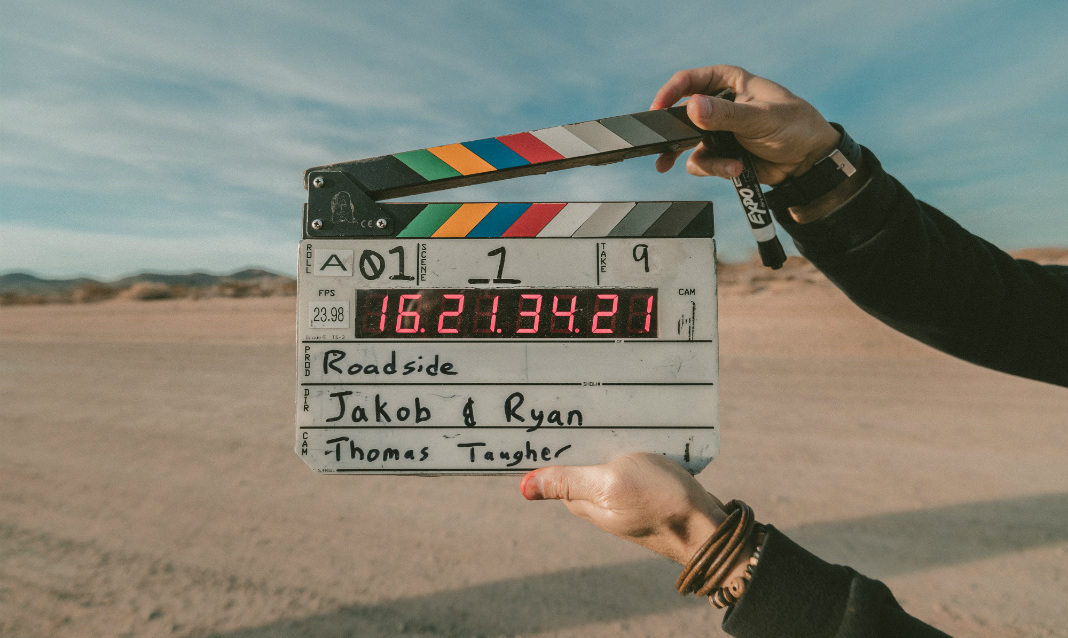 A person's hands holding a clapperboard