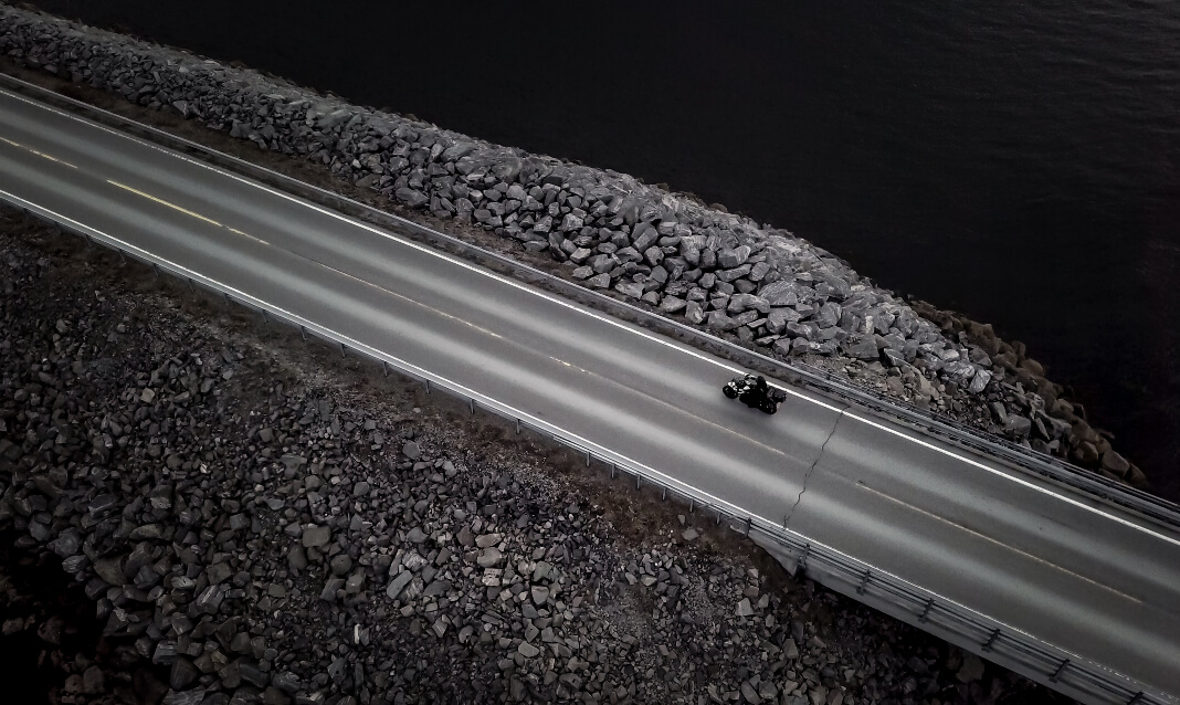 Black and white aerial view of a motorbike on the road