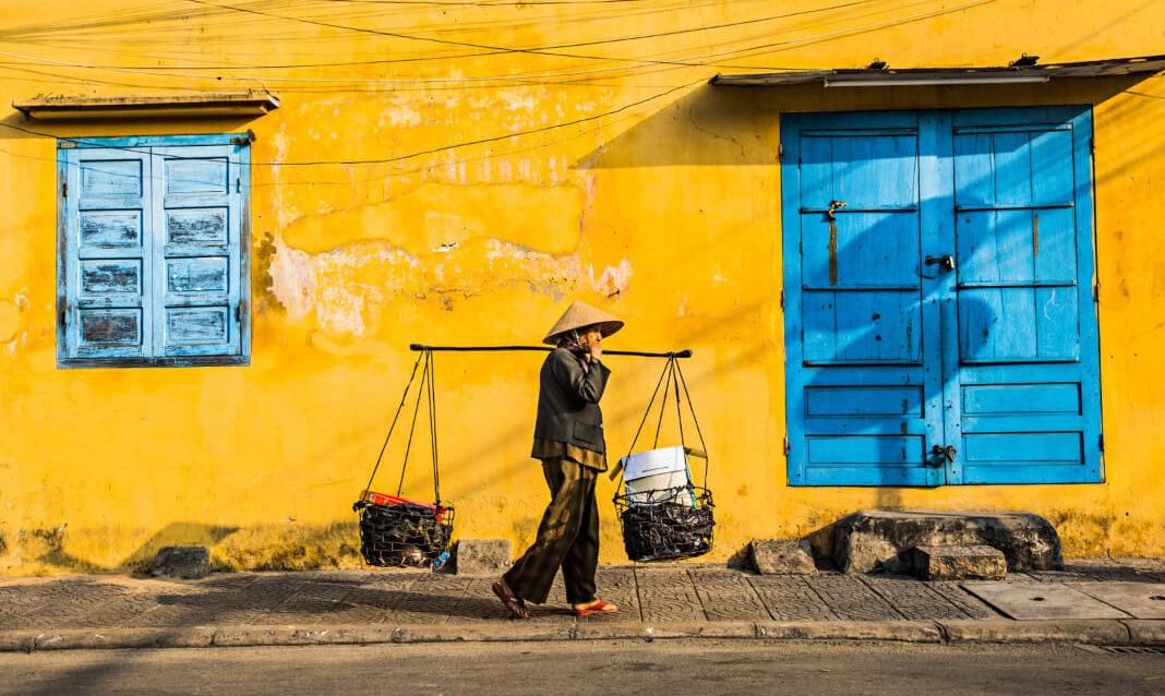 A man carries supplies down the street