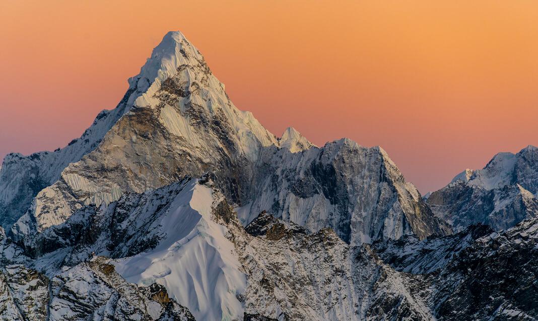 A snowy peak in front of an orange sky