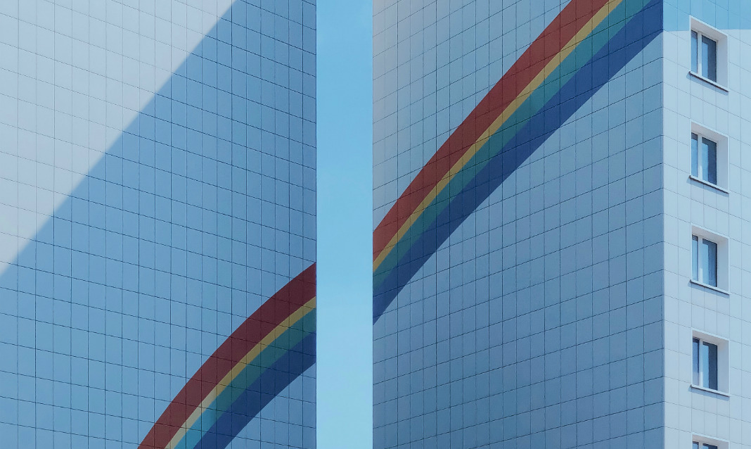 A painted rainbow spans across two buildings, as captured by Patryk Wikalinski