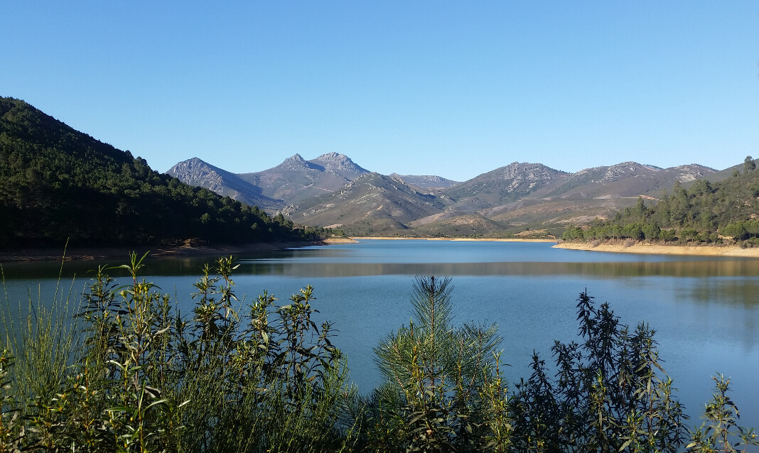 A lake reflects a blue sky with hills surrounding it