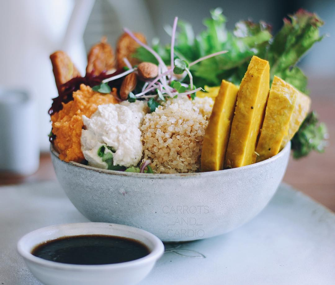 A white bowl of quinoa and other vegan ingredients.