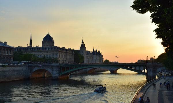 The sun sets behind the Seine River in Paris.