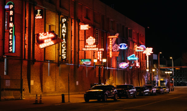 Several neon signs along a street in Edmonton.