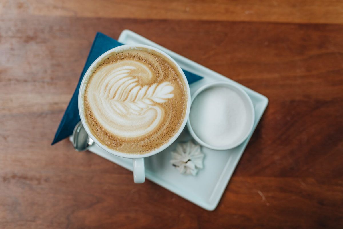 A cup of coffee with latte art sits on a white plate on a brown table.