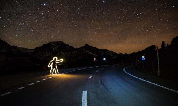 A neon cut-out of a hitchhiker stands on the side of a road at night.
