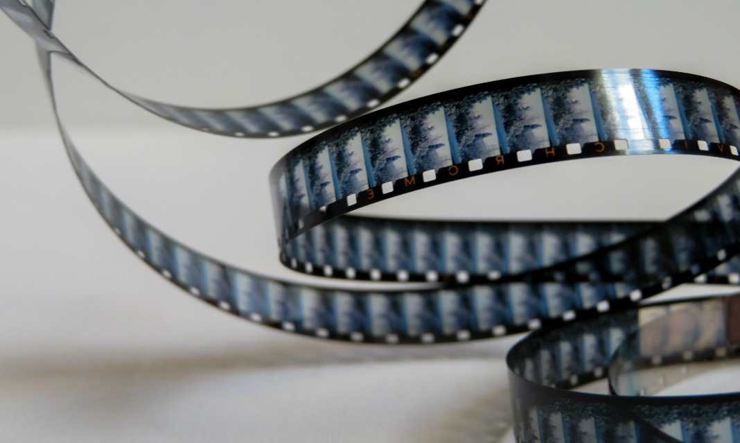 A winding film reel against a gray background