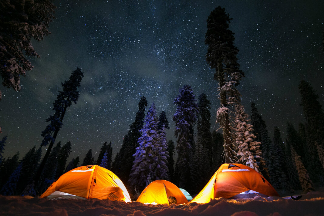 Three tents glowing with light beneath vast night sky in the Sierra National Forest, USA