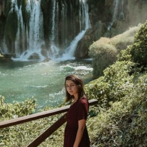 woman in red dress on path by waterfall