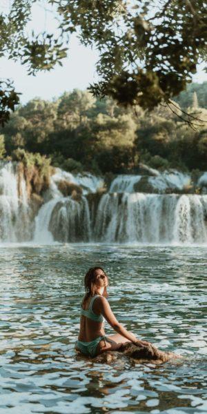 woman sitting in waterfall