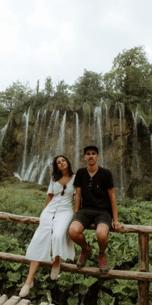 couple sitting on fence by waterfall