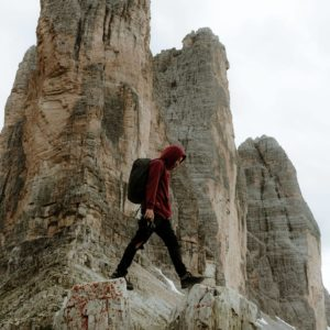 man crossing mountain peaks