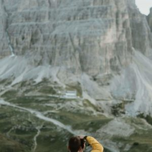 man in yellow jacket photographs mountain