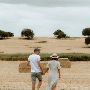 couple walking through grain field