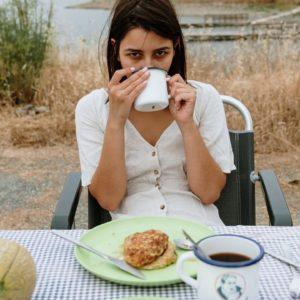 girl eating pancakes on table