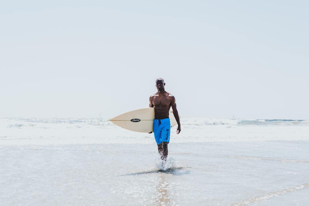 person walking through water with surfboard