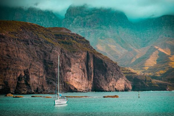 gran canaria - best places for digital nomads - mountains, turqouise sea and boat